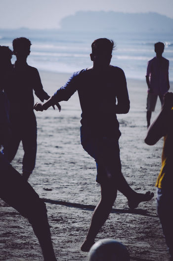 Silhouette men playing on beach against sky during sunset