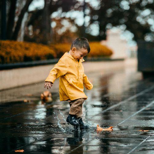 Full length of boy with yellow umbrella in rainy season