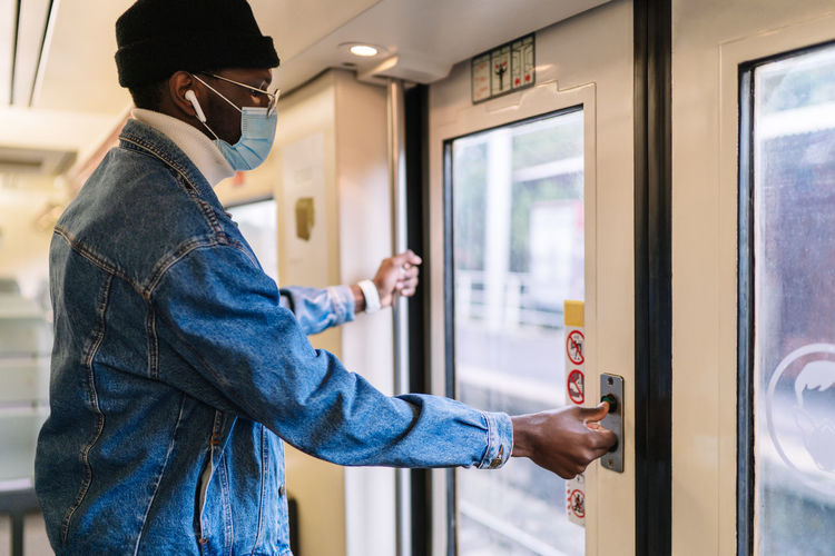 Midsection of man standing by train window