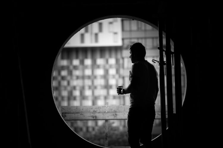 Man Looking Through Circular Window