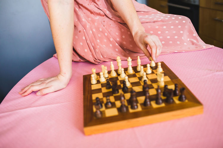Midsection of woman dressed in pink playing chess