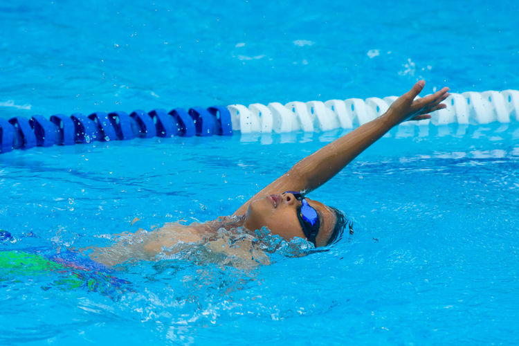 ASIAN BOY SPRINTING IN SWIMMING COMPETITION Arms Raised Athlete Blue Exercising Eyewear Healthy Lifestyle Human Arm Leisure Activity Lifestyles Motion Nature One Person Outdoors Pool Real People Sport Swimming Swimming Pool Swimwear Water Women Young Adult