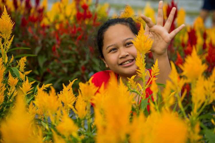 Smiling girl touching yellow flowers at park