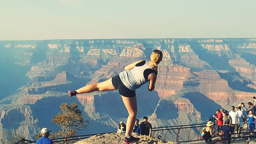 Rear View Of Woman Standing On Leg In Front Of People At Grand Canyon National Park