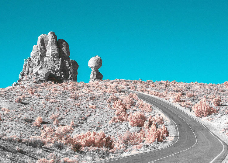 Rock formation on road against clear blue sky