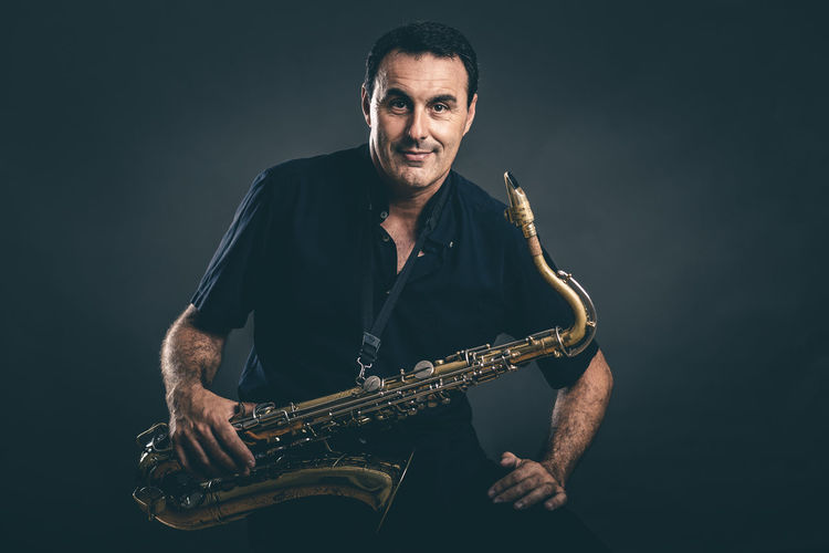 Portrait of adult playing saxophone. Adult Arts Culture And Entertainment Black Background Illuminated Indoors  Jazz Music Lifestyles Looking At Camera Men Music Musical Instrument Musician One Person People Performance Playing Portrait Real People Rock Music Saxophone Studio Shot