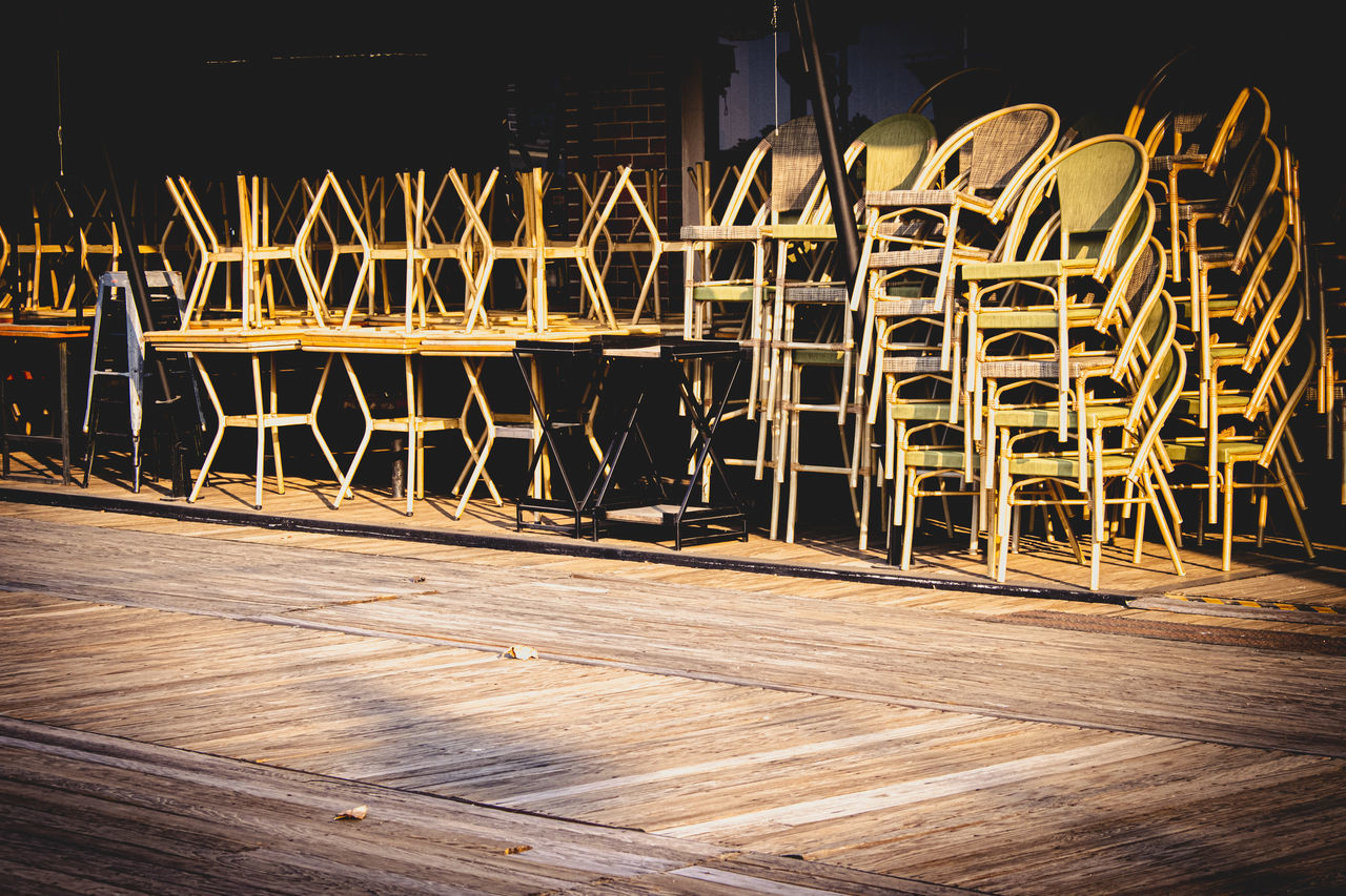 EMPTY CHAIRS AND TABLES IN ROW ON WOODEN FLOOR