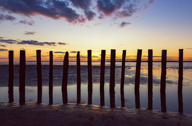 Setting Sun Beach Sea Sunset Horizon Over Water No People Reflection Outdoors Cloud - Sky Sand Wooden Post Tranquility Landscape Nature Scenics Seaside Seascape Sandy Beach Dusk Beauty In Nature In A Row Holidays 14 Wooden Posts Shillouette