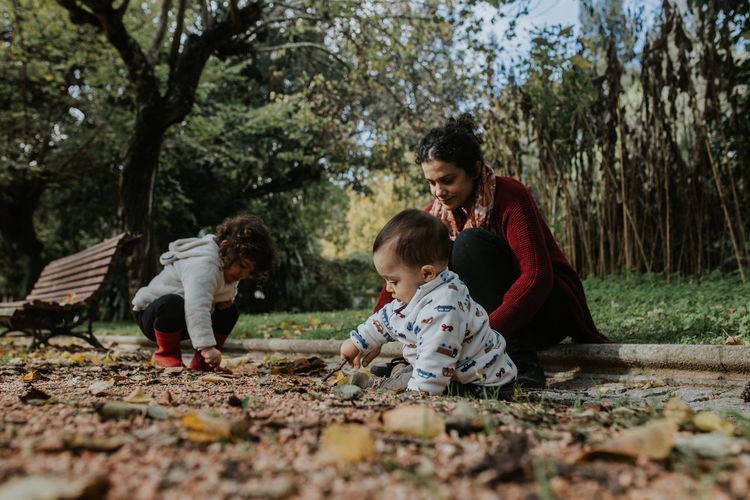 Mother playing with two children outdoors