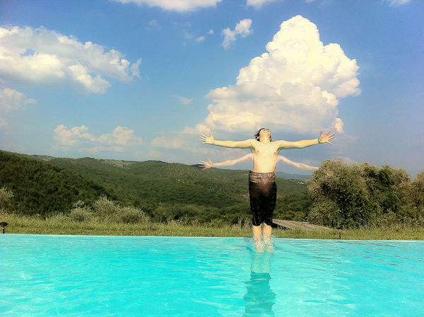 Young man jumping into the Pool with a great scene of clouds behind him Arms Outstretched Showcase June Cloud Cloud - Sky Day Enjoyment Freedom Full Length Fun Idyllic Jumping Leisure Activity Lifestyles Nature Outdoors Scenics Sky Tranquil Scene Tranquility Vacations Water The Innovator Flying
