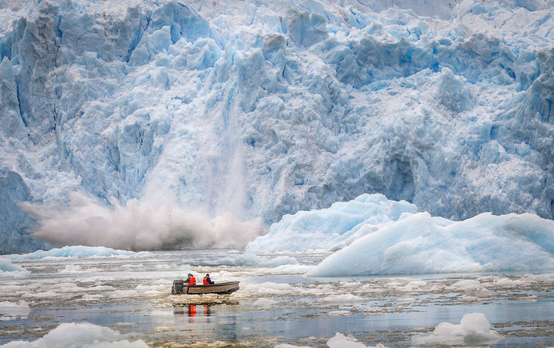 People In Boat On Frozen Lake Against Glacier