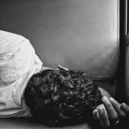 Close-up of man lying on train seat