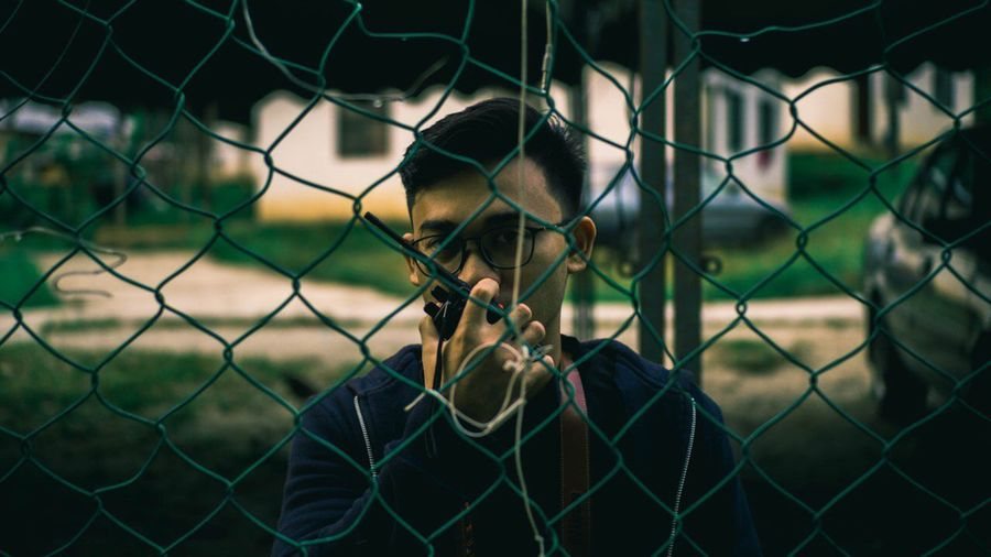 Portrait of man talking on walkie-talkie seen through chainlink fence