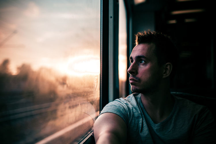 Young Man Looking Through Train Window During Sunset