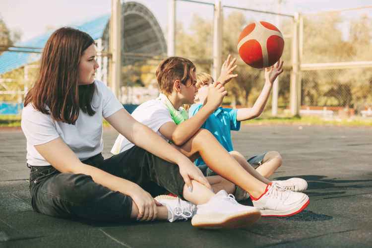 Cheerful high school students sit on the basketball court, relax after the game, talk and laugh.