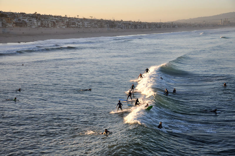 People surfboarding on waves in sea during sunset