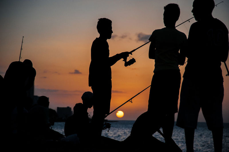 Silhouette people fishing by sea against sky during sunset