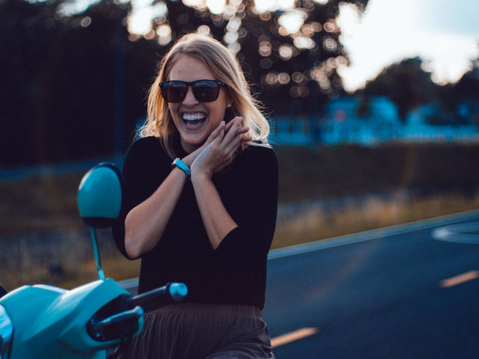 Portrait of cheerful young woman wearing sunglasses sitting on motor scooter