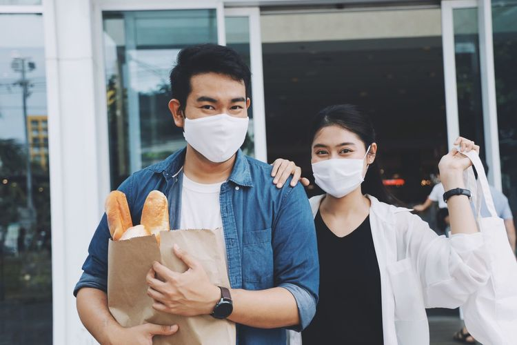 Portrait of smiling couple wearing flu mask holding shopping bag standing outdoors