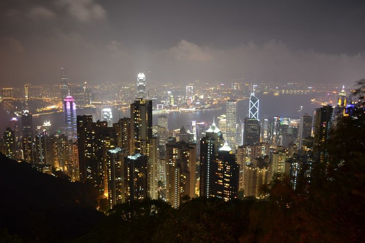 High angle view of victoria harbor amidst illuminated buildings in city