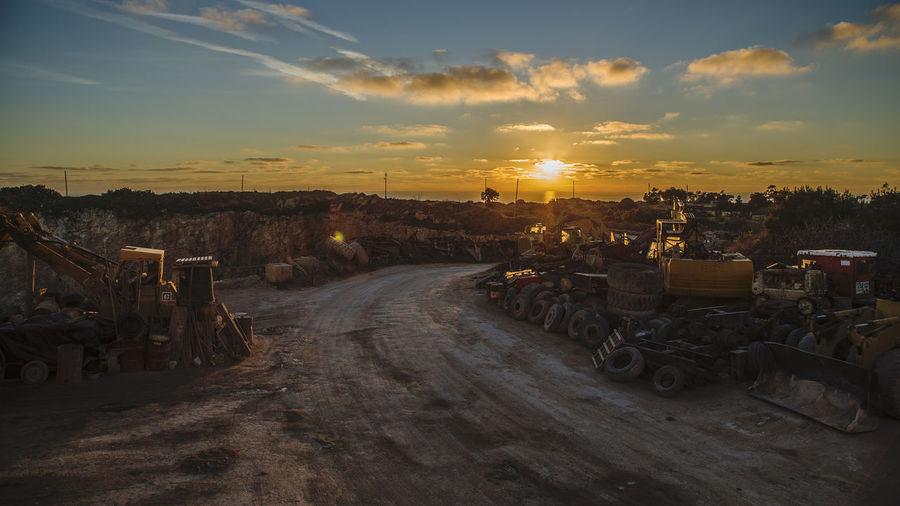 Road Amidst Junkyard Against Sky During Sunset