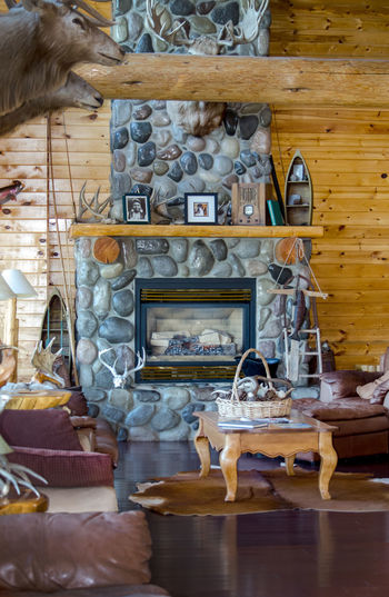 September 2017 Wyoming USA; a beautiful and rustic living room in wyoming shows off natural accents, a stone fireplace and wildlife trophy heads on the walls Deer Elk Interior Decorating Moose Animals Cabin Day Editorial Photography Indoors  Large Group Of Objects Living Room Natural Accents No People Rustic Style Stone Fireplace Table Trophy Heads Wildlife Wood And Stone Structure Wyoming Architecture The Architect - 2018 EyeEm Awards