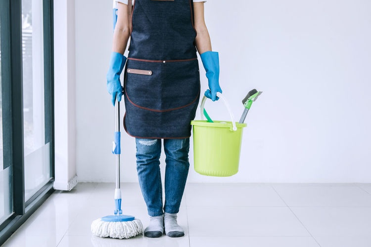 Low section of cleaner with mop and bucket on tiled floor