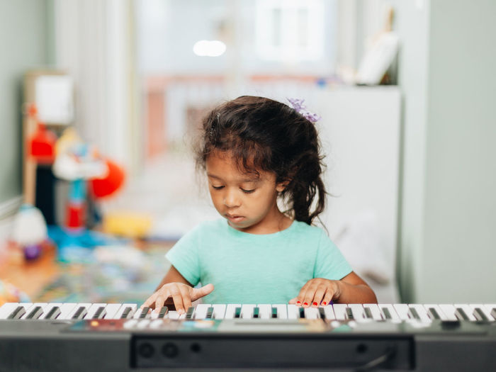 Cute girl learning piano at home