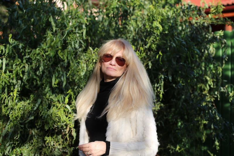 Portrait of senior woman standing against trees