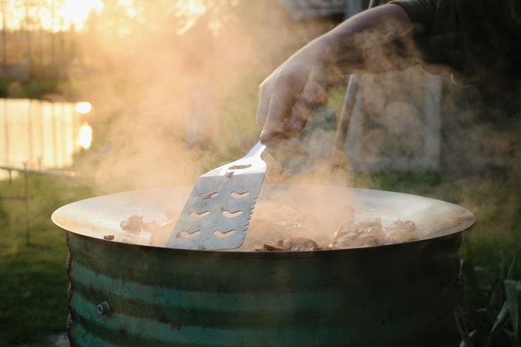 Cropped Hand Of Person Making Food In Container At Backyard During Sunset