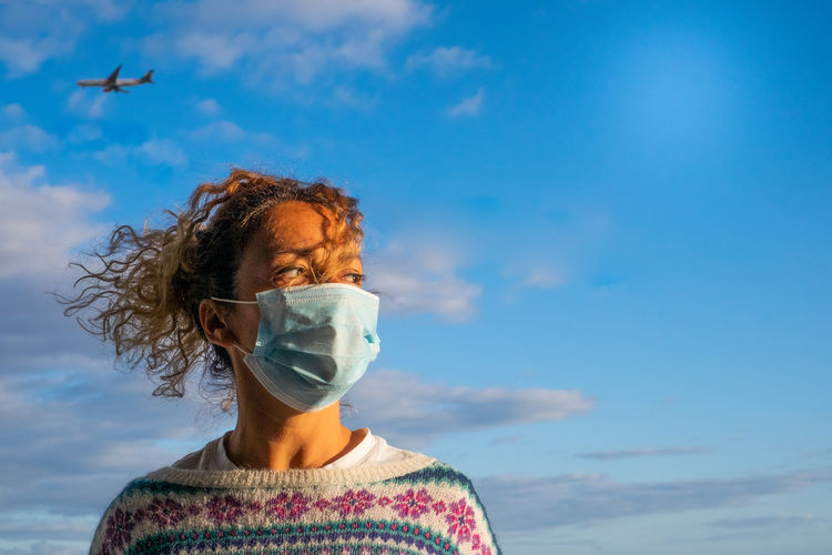 Thoughtful woman wearing mask while standing against sky