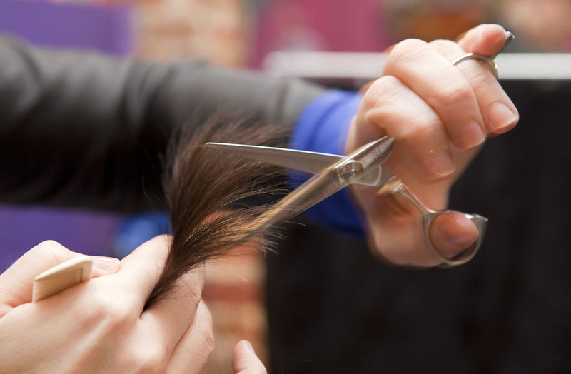 Cropped hands of hairdresser cutting customer hair at salon