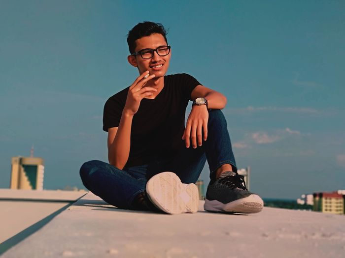 Smiling young man smoking cigarette while sitting on building terrace against blue sky