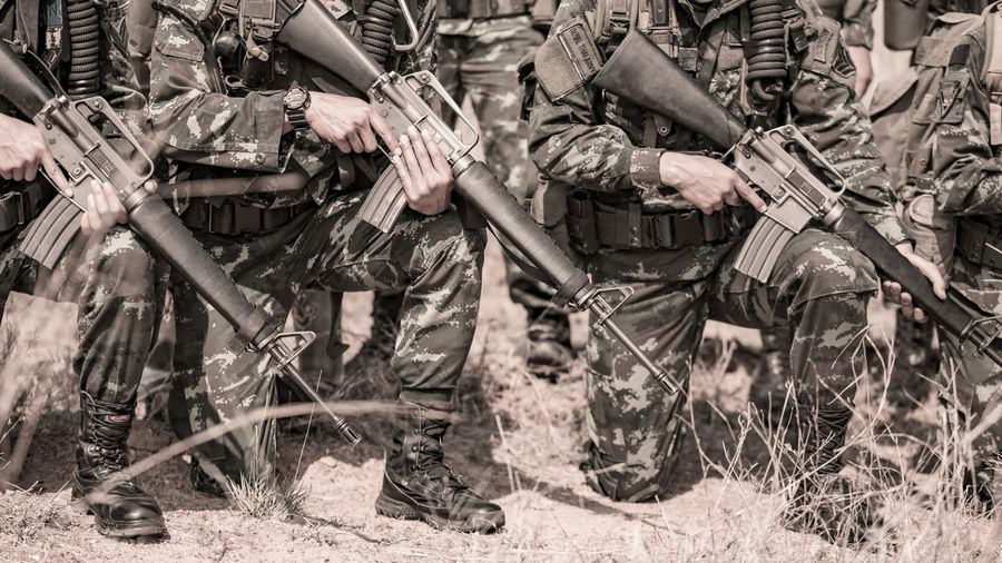 Low section of army soldiers with rifle on field