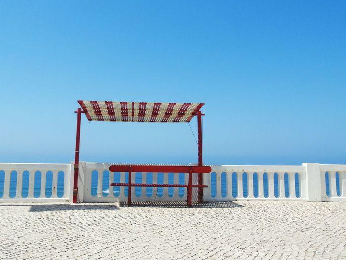 Bench On Bridge Over Sea Against Clear Blue Sky