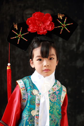 Portrait of girl wearing traditional clothing standing against wall