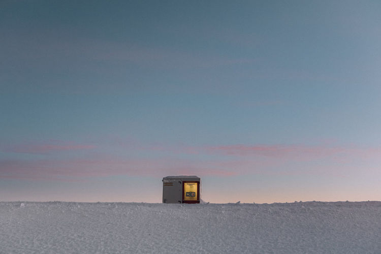 Built structure on snow covered land against sky during sunset