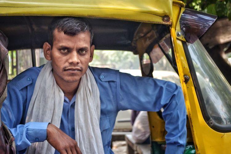 Portrait of man sitting in auto rickshaw