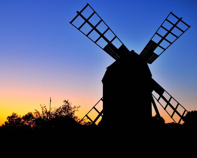 Low angle view of silhouette traditional windmill against sky at sunset