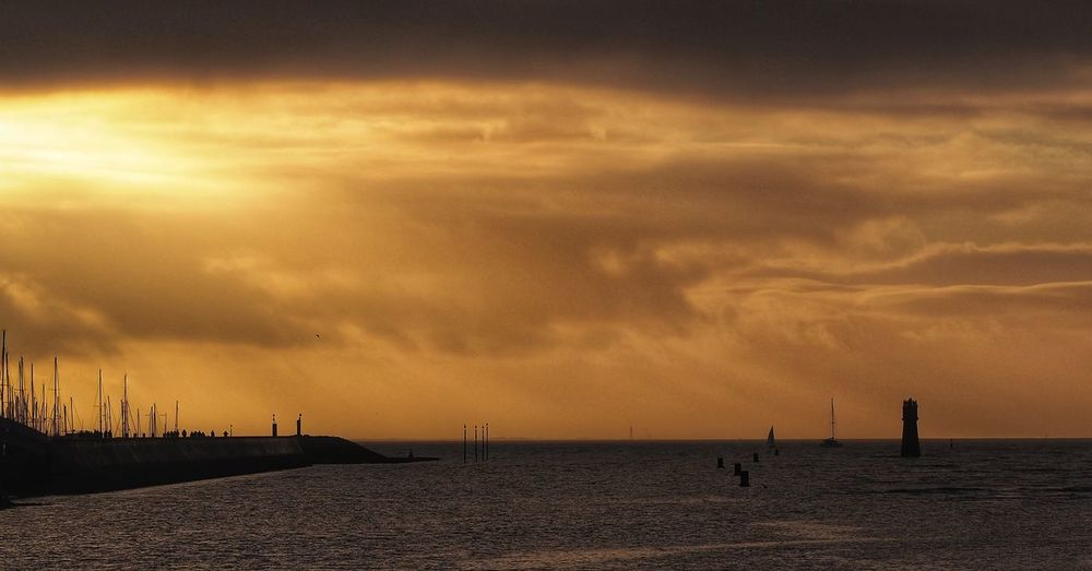 Silhouette sailboats in sea against sky at sunset