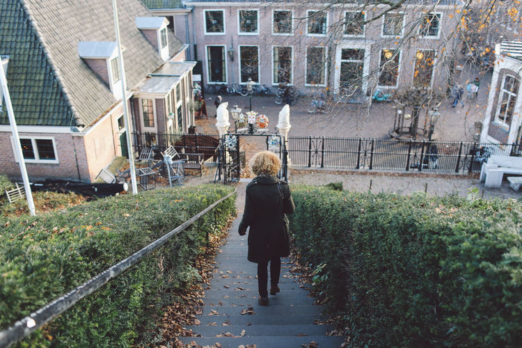Rear View Of Woman Walking Down Steps In City