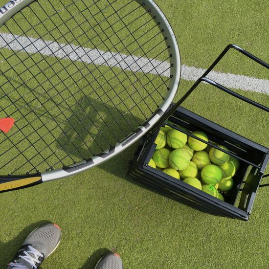 Low Section Of Man Standing With Tennis Racket By Balls In Container At Court
