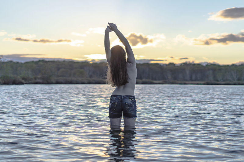 Adult Arms Raised Beauty In Nature Hairstyle Human Arm Lake Leisure Activity Lifestyles Nature One Person Real People Rear View Rippled Scenics - Nature Sky Standing Sunset Water Waterfront Women