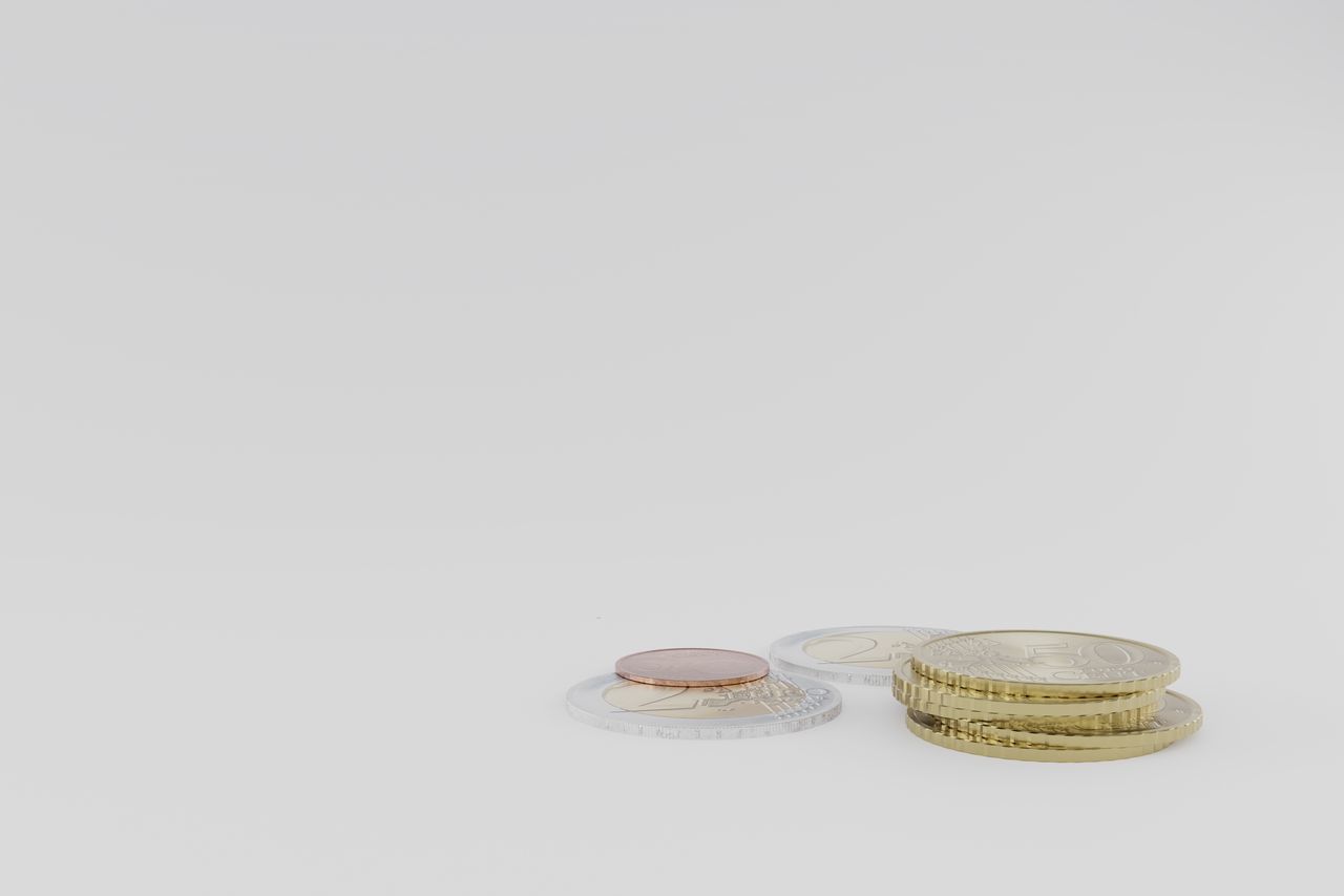CLOSE-UP OF COINS IN WHITE BACKGROUND