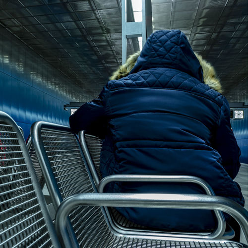sitting man Seats Row Subway Station Modern Architecture Rear View One Person Transportation Architecture Mode Of Transportation Indoors  Real People Seat Day Public Transportation Travel Men Blue Sitting Standing Built Structure Rail Transportation Hood Subway Train Hood - Clothing