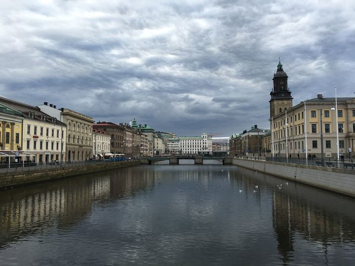 View of river in old town against cloudy sky