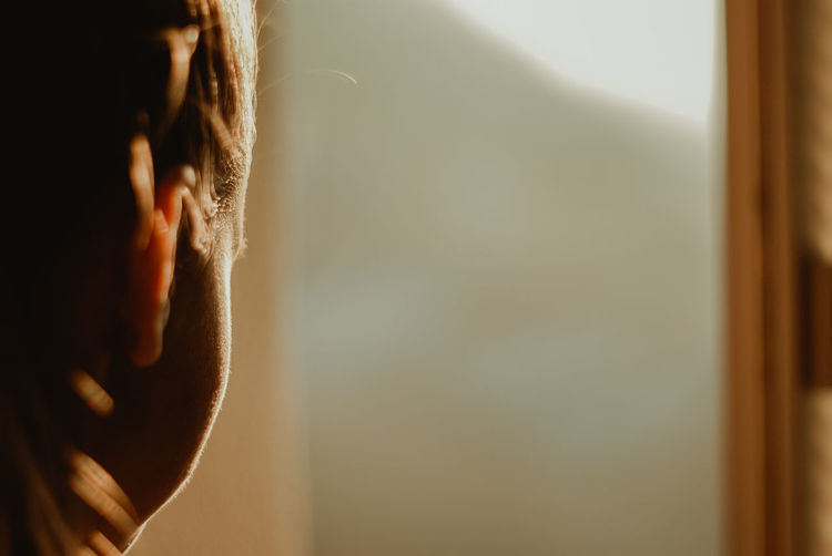 Close-up portrait of man against window