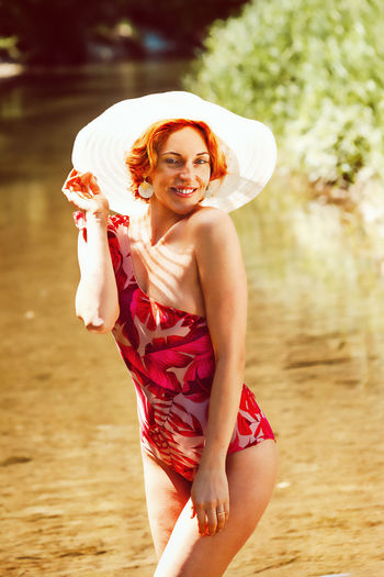 Woman wearing swimwear while standing in lake