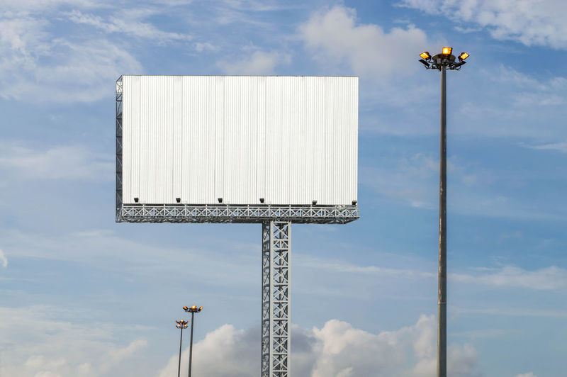 Big Billboard Sky Cloud - Sky Low Angle View Nature Lighting Equipment No People Day Outdoors Pole Fuel And Power Generation Built Structure Architecture Floodlight Tall - High White Color Technology Environmental Conservation Communication Beauty In Nature Billboard Blank