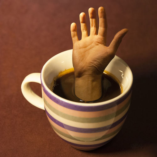 Digital composite image of cropped hand in coffee cup on table